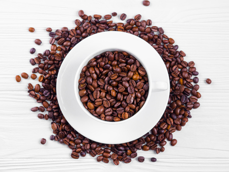 Porcelain white coffee cup and roasted beans on shabby wooden background. Top view.