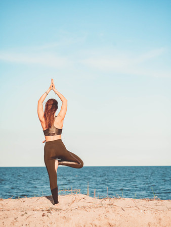 Young beautiful sporty woman in green clothing doing yoga asana on sea sandy beach near water. Girl practicing exercises. Health concept. Copy space. Stock Photo