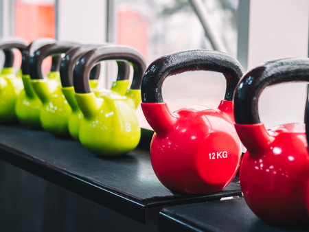 Rows of heavy metal dumbbells on rack. Sports Training Equipment in modern sports club or in the gym. Sport and health concept.