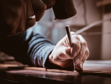 Close up of leather craftsman working with natural leather using hammer. Handbag master at work in local workshop. Handmade concept. Male shoemaker creating product with textile