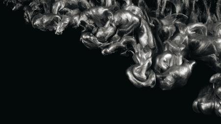 Silver ink in water shooting with high speed camera. Paint dropped, reacting, creating abstract cloud formations and metamorphosis on black. Art backgrounds. Archivio Fotografico