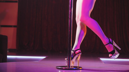 Young slim woman pole dancing striptease with pylon in night club. Beautiful girl on stage