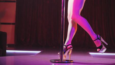 ナイトクラブでパイロンとストリップショーを踊る若いスリムな女性ポール。ステージ上の美しい女の子