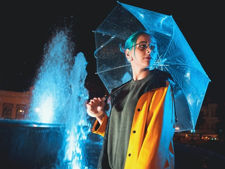 Young pretty girl with blue dyed hair in yellow raincoat and with transparent umbrella stands near fountain. Night neon illumination of city. Portrait of stylish hipster with glasses.