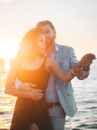 Young spanish couple against sunset sea background. Small resort european city. Man and woman dancing latin american sensual dance: bachata, salsa or kizomba.