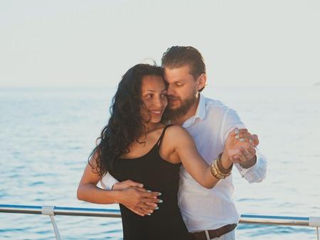 Retrato de joven atractiva pareja bailando bachata latina cerca del mar. Baile realizado por un profesional en la playa del océano. Mujer vestida de negro. Salsa sensual, rumba.