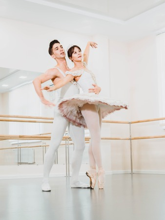 Training before performance. Man dancing classical ballet, he rotating pretty woman in white tutu dress in gym or ballet hall. Couple perform sensual dance. Minimalism interior.