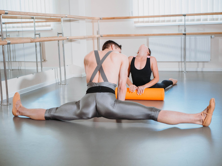 Preparation of body before performance in ballet studio. Male dancer and ballerina warming up near barre on rehearsal.