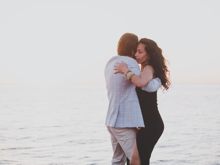 Young spanish couple against sunset sea background. Small resort european city. Man and woman dancing latin american sensual dance: bachata, salsa or kizomba.