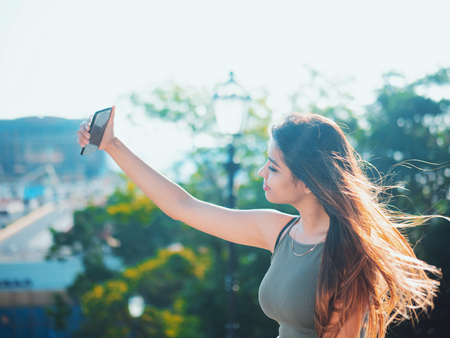 Portrait of young attractive female in fashion outfit making selfie outdoor while sitting on stairs. Beautiful woman with oriental face smiling to smartphone camera.