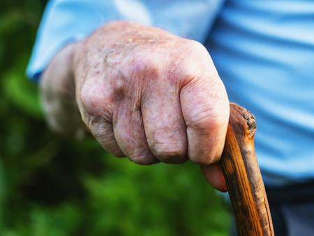 wrinkled old man' hands crossed on the stick. Close-up of a pensive grandfather sitting alone outdoors and rests on a cane. Imagens