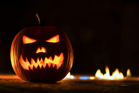 Horrible symbol of Halloween - Jack-o-lantern. Scary head of pumpkin in hell fire flames. Half of orange gourd on the left side. Glowing face, trick or treat. Copy Space.