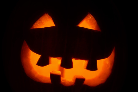 Close up portrait of carved pumpkin head Jack-o-lantern. Terrible symbol with eyes and scary grin. Halloween party art decoration. Silhouette of facial features on black background