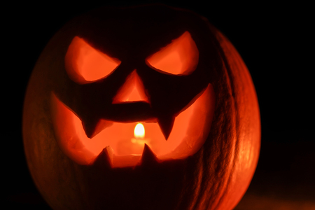 Orange mad pumpkin as head of Jack-o-lantern with carved eyes and wicked smirk. Scary symbol of Halloween. Gourd on the left side. Stock Photo
