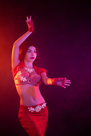 Frau im exotisch leuchtend roten Kostüm bewegt ihren Körper sexuell. Sexy traditionelles orientalisches Bauchtänzerinmädchen, das auf Neonrauchhintergrund tanzt. Muslime, Versuchungskonzept