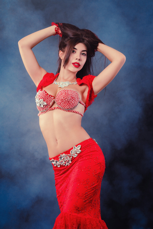 Woman in exotic shining red costume sexually moves her body. Sexy traditional oriental belly dancer girl dancing on neon smoke background. Muslims, temptation concept Standard-Bild