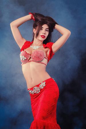 Vrouw in exotisch glanzend rood kostuum beweegt seksueel haar lichaam. Sexy traditionele oosterse buikdanseres meisje dansen op neon rook achtergrond. Moslims, verleiding concept