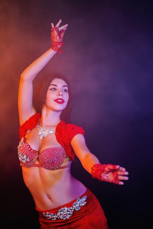Verlockendes traditionelles orientalisches Bauchtänzerinmädchen, das auf lila Neonrauchhintergrund tanzt. Frau in exotischem rotem Kostüm bewegt sexuell ihren halbnackten Körper. Standard-Bild