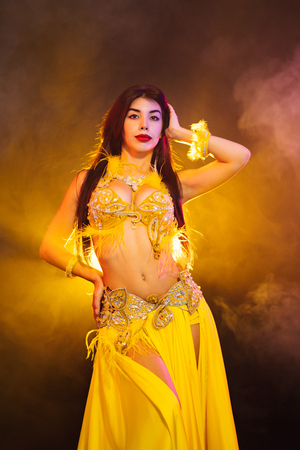 Alluring sexy traditional oriental belly dancer girl dancing on yellow neon smoke background. Woman in exotic costume with feathers sexually moves her semi-nude body