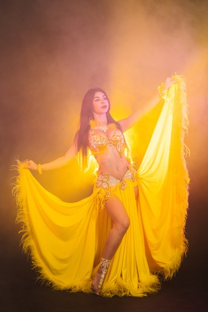 Alluring sexy traditional oriental belly dancer girl dancing on yellow neon smoke background. Woman in exotic costume with feathers sexually moves her semi-nude body Stock Photo - 109404891