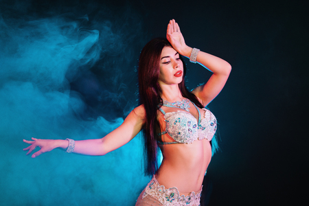 Woman in exotic costume sexually moves semi-nude body. Sexy traditional oriental belly dancer girl dancing on blue neon wall. Muslims, temptation concept. Spectacular show