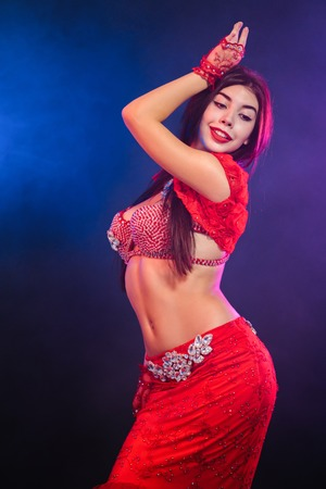 Verlockende traditionelle orientalische Bauchtänzerin, die auf lila Neonrauchhintergrund tanzt. Frau in exotischem rotem Kostüm bewegt ihren halbnackten Körper sexuell.