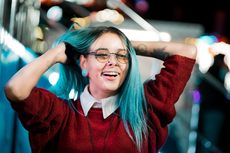 Hipster girl waving head in different directions, playing with dyed blue hair. Woman with nose piercing, transparent glasses, ears tunnels, unusual hairstyle in amusement park