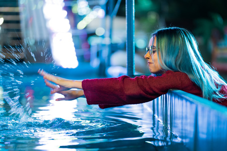 Hipster girl with blue dyed hair having fun, sprays pool water. Woman with nose piercing, transparent glasses, unusual hairstyle in amusement night park