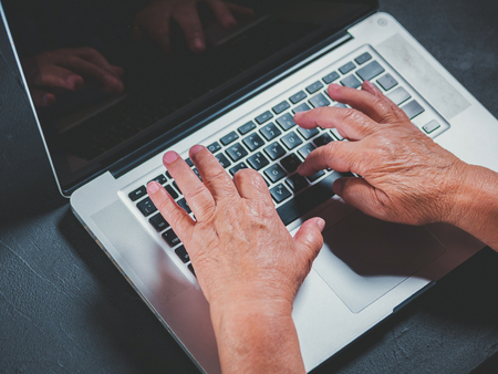 Grandmother works behind laptop, typing on keyboard with her old hands with wrinkles. Modern old pensioner working from home. Close up view of elderly womans hands.