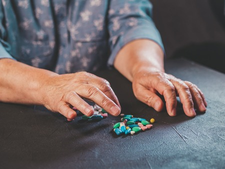 Grandmother counts multicolored tablets on black table at home. The concept of old age, medication, treatment. Close-up of hands with wrinkles. Banco de Imagens