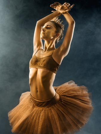 Portrait of beautiful young ballet dancer with shining golden skin on black background. Body art with gold paint. Ballerina in tutu dancing on smoke stage