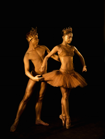 Professional, emotional ballet dancers with crowns on dark smoke scene performed by sexual couple king and queen with golden body art. Shining gold skin