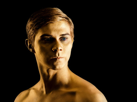 Close up portrait of handsome young ballet dancer with shining golden skin on black background. Body art with gold paint. Fashion style. Man model portrait