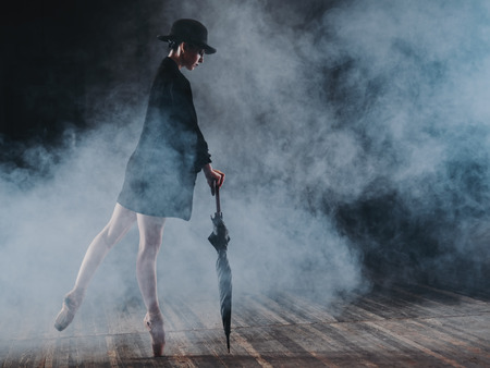 Ballerina in black long jacket and sexy bodysuit dancing on stage with magic light and smoke. Young attractive dancer in ballet shoes pointe with umbrella