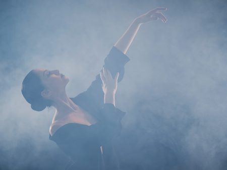 Young beautiful ballerina on smoke stage dancing modern ballet. performs smooth movements with hands. Woman in black costume on scene
