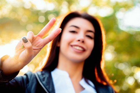 Young beautiful woman showing gesture of PEACE and smiling to camera on autumn park background.