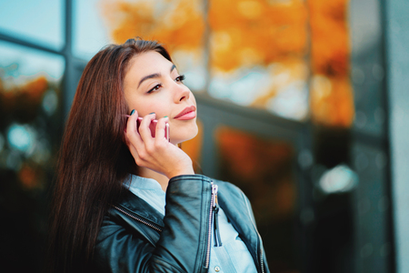 Business woman with smartphone close up near office building. Girl have conversation with cell phone. Beautiful caucasian young woman talking with mobile device. Banco de Imagens