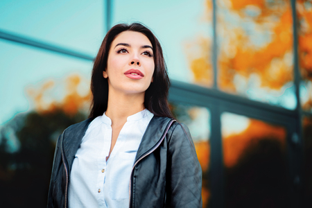 Portrait of young happy business woman near office building. Beautiful caucasian student girl in white sexy blouse standing in the autumn street