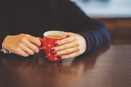 Cup of tea. Female hands holding hot drink at the kitchen.