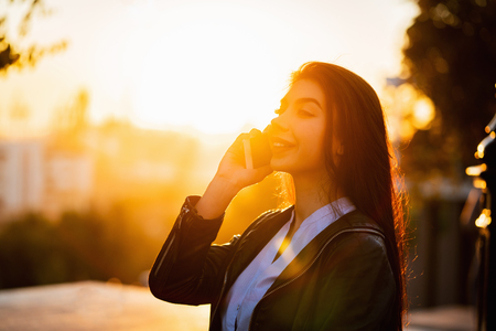 Business woman with smartphone close up in autumn city, sunset light. Girl have conversation with cell phone. Beautiful caucasian young woman talking with mobile device Banco de Imagens