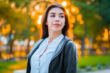 Portrait of young happy business woman in the city. Beautiful caucasian student girl in white sexy blouse standing in the autumn street. Banco de Imagens