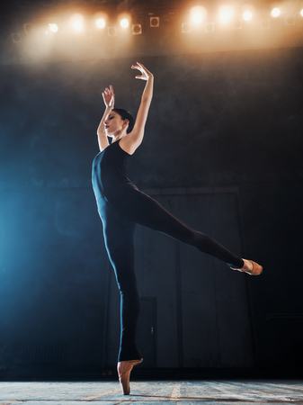 Young beautiful ballerina on smoke stage dancing modern ballet. performs smooth movements with hands against spotlights background. Woman in black costume on scene