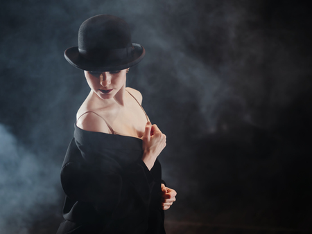Woman in black costume on scene. Young beautiful ballerina on smoke stage dancing modern ballet. performs smooth movements with hands against spotlights background. Banco de Imagens