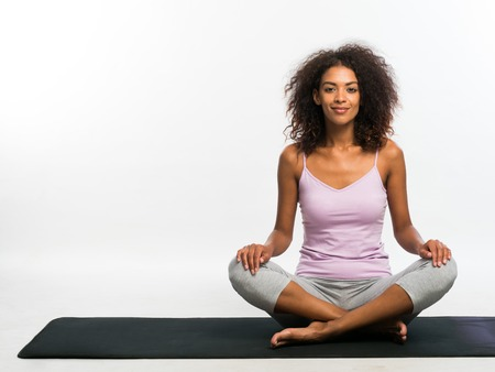 Happy african american woman in comfortable sports wear sitting on black yoga mat over white wall background. Girl concentrated on her practice Banco de Imagens