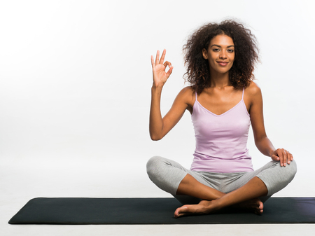 Happy african american woman showing ok sign while sitting on black yoga mat over white wall background. Girl in comfortable sports wear concentrated on her practice.