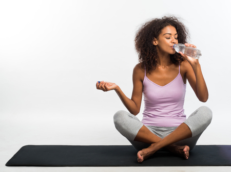 Happy african american woman drinking fresh water from bottle while sitting on black yoga mat over white wall background. Girl in comfortable sports wear. Healthy lifestyle Banco de Imagens