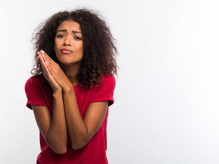 Attractive african woman in red t-shirt praying, begs over white background. Mixed race girl begging someone