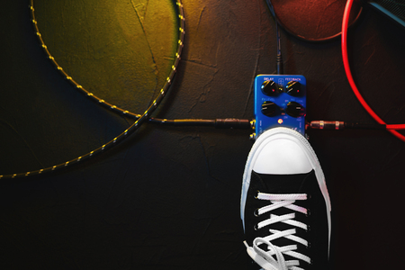 Close up of guitar player foot pressing pedal. Musician uses music effect loop machine. Man in trendy sneakers, his foot playing at stage during concert. Macro view. Copy space