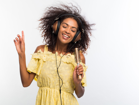 Young pretty african american woman in yellow dress singing and dancing with hair dryer instead microphone at white wall. Black girl having fun isolated on background. Banco de Imagens