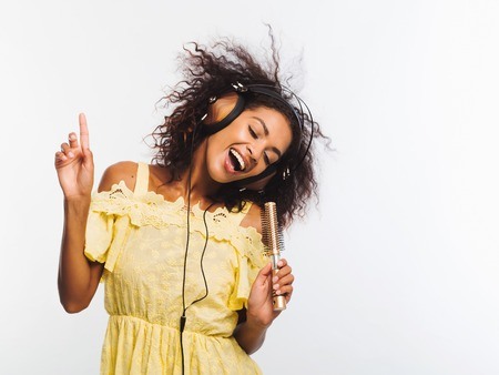 Young pretty african american woman in yellow dress singing and dancing with hair dryer instead microphone at white wall. Black girl having fun isolated on background. Stock Photo